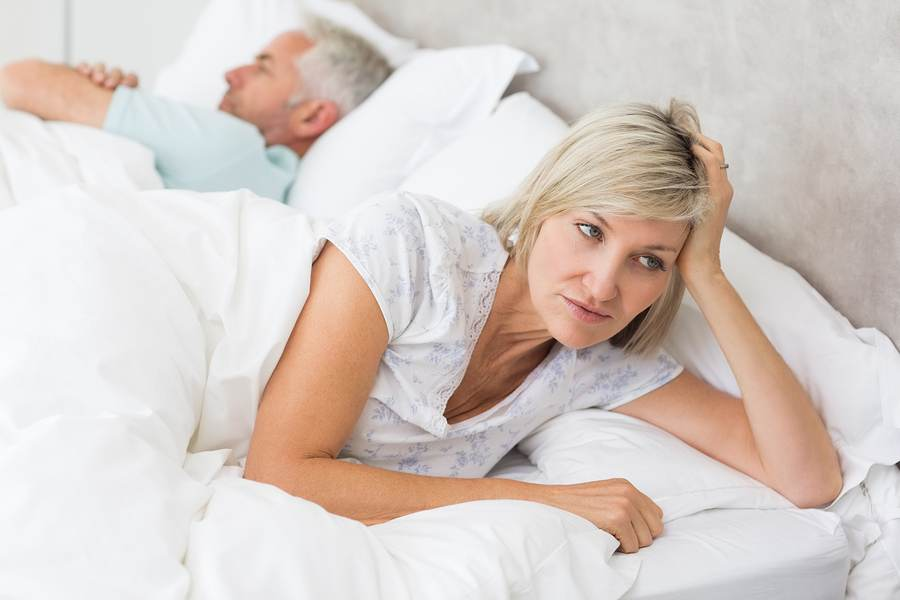 Close-up of a tensed woman lying besides man in bed at home (Bigstock image)