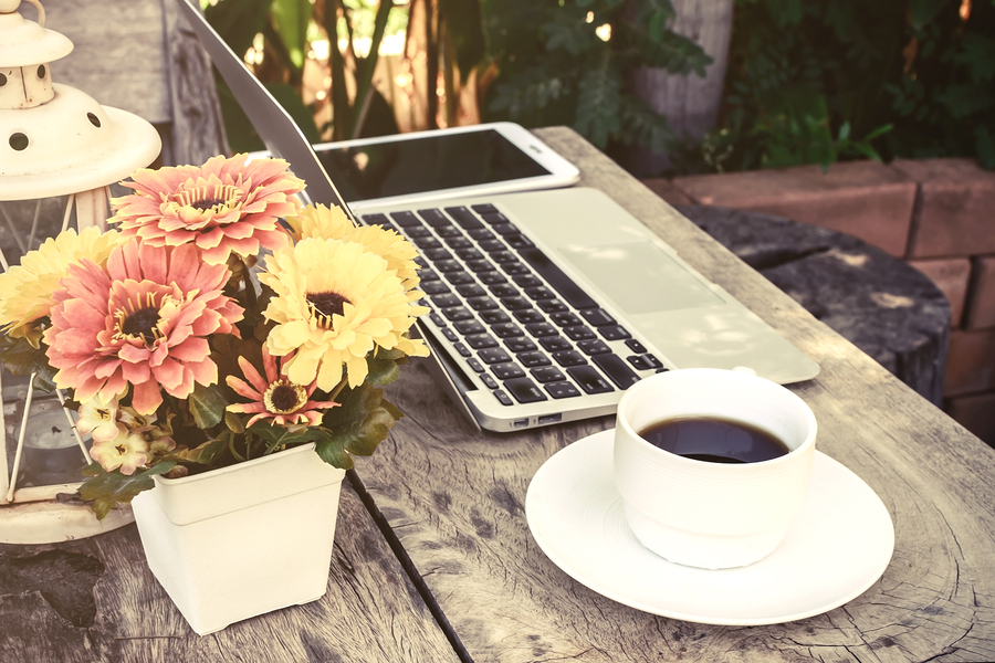 a cup of coffee and laptop on wood floor with flower vintage style